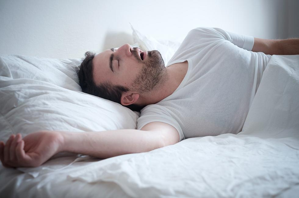 A young male with a beard lying on his back and breathing with his mouth open, which is a clear sign of sleep apnea in Midland
