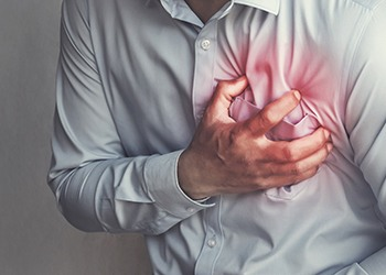 A man clutching his chest because he is experiencing a heart attack