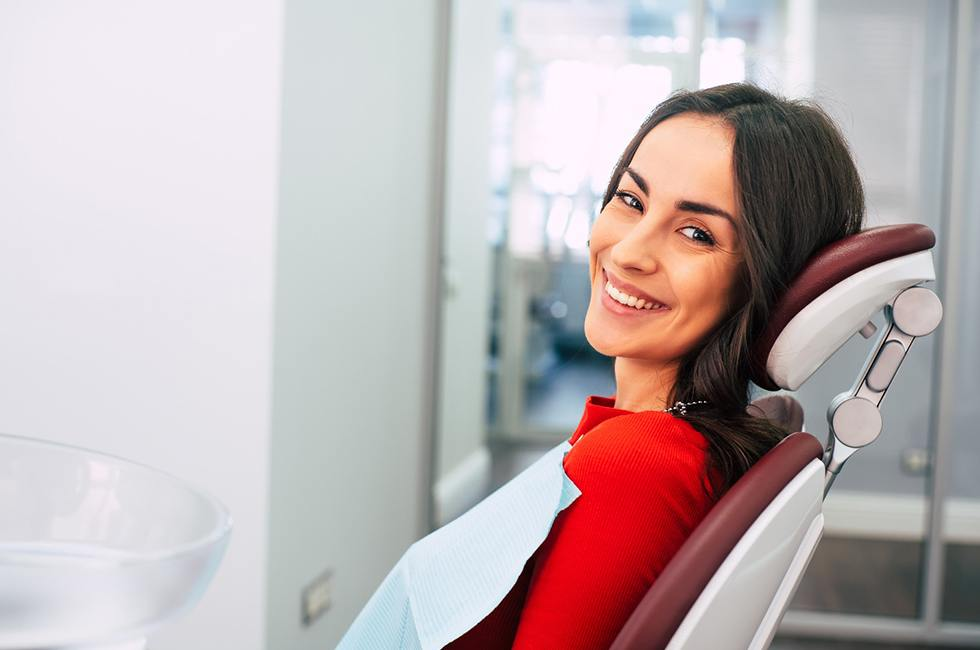 A young woman seated in the dentist's chair and waiting to see her dentist in Midland for treatment