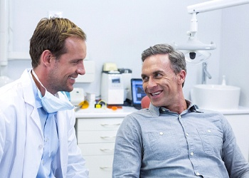 Dentist and patient discussing how dental implants work in Midland