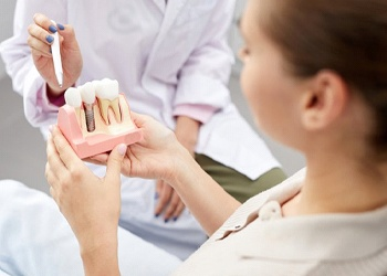 Patient learning how dental implants work in Midland with model