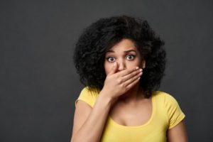 Concerned woman covering her mouth because of bad oral health habits