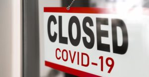 "Door sign reading ""CLOSED COVID-19"" until your Midland dentist reopens."