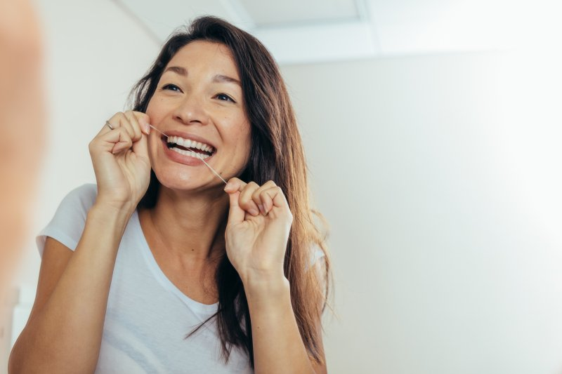 Woman smiling while flossing her teeth