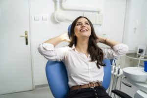 Woman smiles and relaxes while visiting Midland sedation dentist