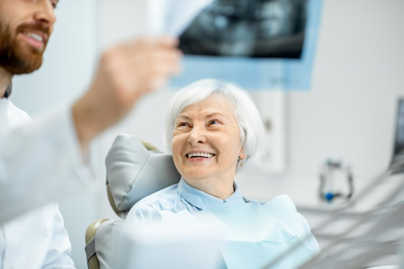 Dentist showing smiling woman X-ray