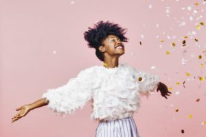 Woman throws confetti celebrating New Year's resolutions from Midland dentist