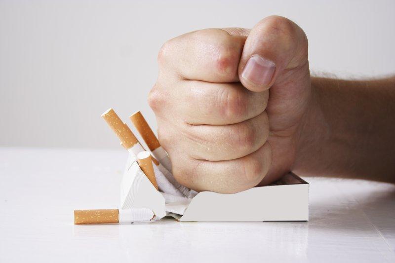 Fist crushing box of cigarettes