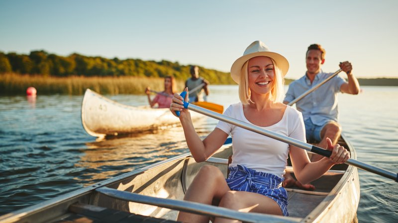 Smiling couple canoeing with friends on the lake